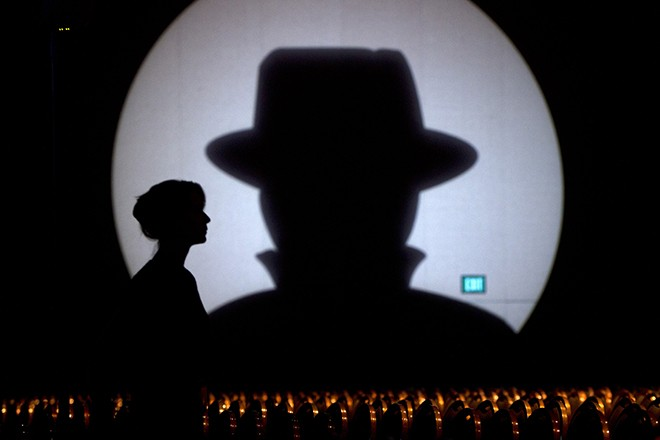 Speaker liaison Genevieve Netter is silhouetted against a Black Hat logo during the Black Hat USA 2014 hacker conference at the Mandalay Bay Convention Center in Las Vegas