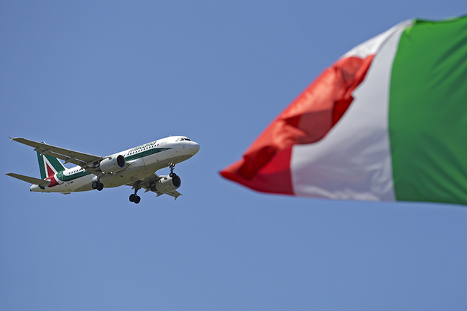 An Italy flag flutters as an Alitalia airplane approaches to land at Fiumicino airport in Rome