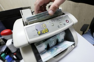 An employee uses a machine while counting Russian ruble banknotes at a private company's office in Krasnoyarsk