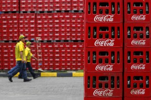 Workers walk at PT Coca-Cola Amatil Indonesia's factory in Cibitung