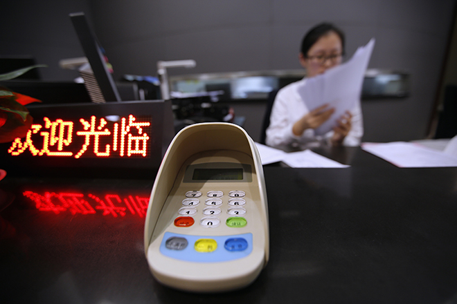 An employee of an Industrial and Commercial Bank of China Ltd (ICBC) branch, part of the Shanghai Free Trade Zone, works at her desk during a government organized media tour in Shanghai