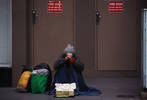 A homeless man begs for money on the footpath of a main street in central Sydney
