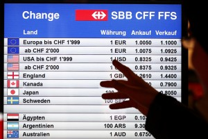 A man looks at  a board showing currency exchange rates in Bern