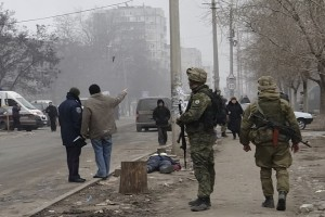 Ukrainian servicemen guard a street, near the body of a victim killed by a recent shelling of a residential sector, in Mariupol, eastern Ukraine