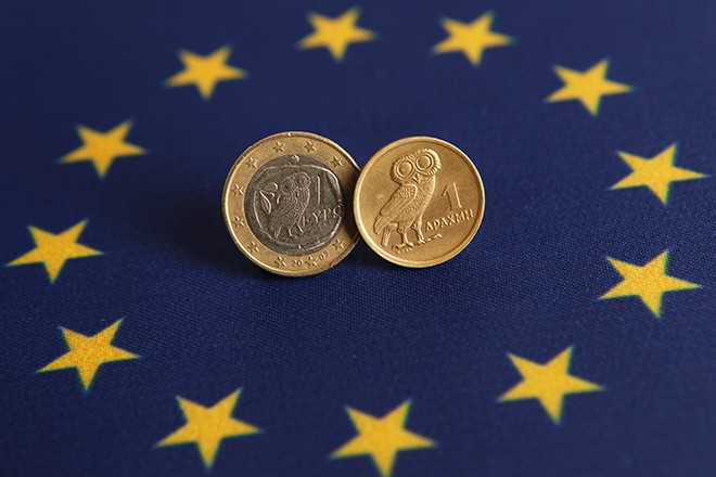 Picture illustration of one Euro and Greek Drachma coins displayed on an European flag