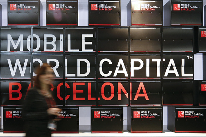 A woman walks past advertising while attending during the Mobile World Congress in Barcelona