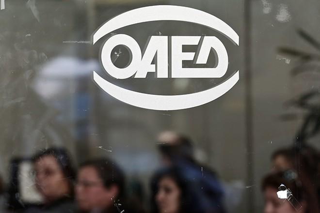 People wait inside a Greek Manpower Employment Organisation office in Athens