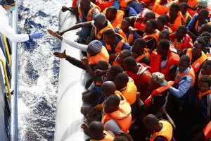 Handout photo shows a group of 104 sub-Saharan Africans on board a rubber dinghy preparing to board the NGO Migrant Offshore Aid Station ship Phoenix some 25 miles off the Libyan coast