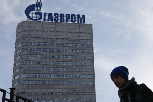 A woman walks along the footpath near the headquarters of the Gazprom company in Moscow