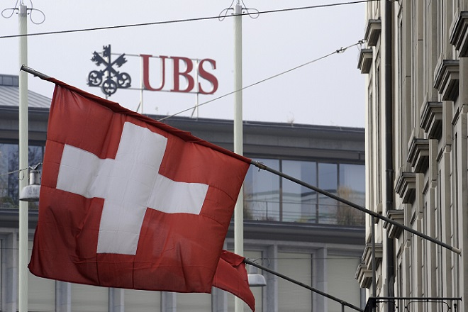 A Swiss flag is seen in front of an UBS logo on Swiss bank UBS headquarters in Zurich