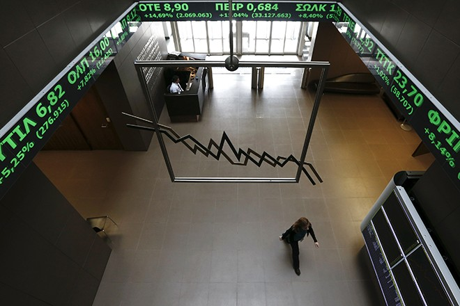 A woman walks inside the Athens stock exchange as a stock ticker shows stock options making major gains, inside the Athens stock exchange building