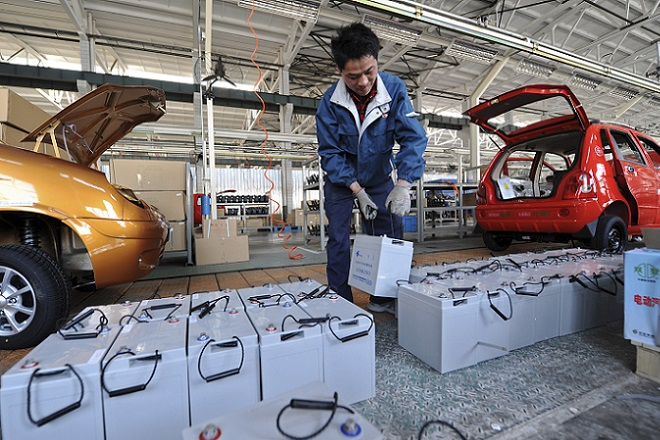 A employee carries a battery as he works on an assembly line of electric cars at a factory in Jinan