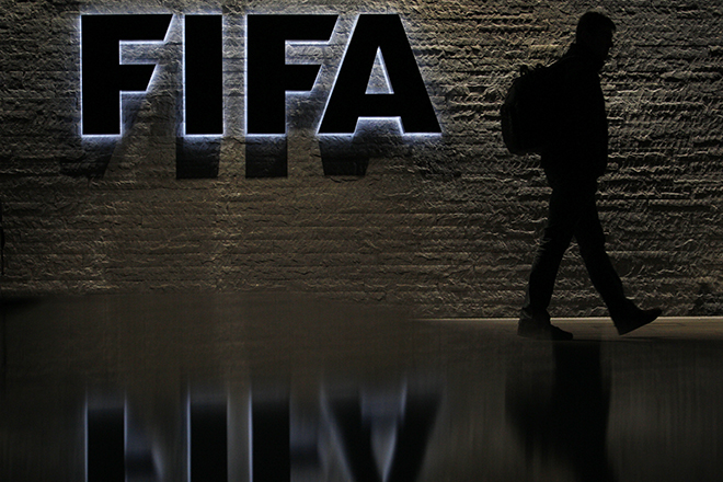 A man is silhouetted as he makes his way past the main entrance of FIFA headquarters, the Home of FIFA, in Zurich October 20, 2010.  REUTERS/Christian Hartmann  (SWITZERLAND - Tags: SPORT SOCCER) - RTXTNHL