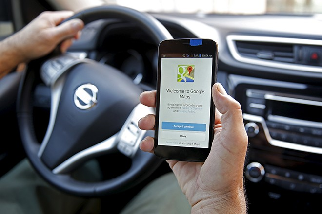 A man holds a smartphone, with the Google Maps app open, in Sarajevo, April 15, 2015. REUTERS/Dado Ruvic - RTR4XGCE