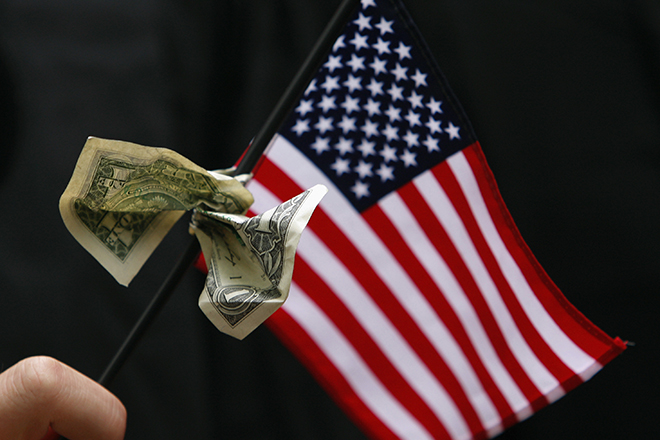 A student graduating from Harvard's Business School holds a U.S. flag with a dollar bill tied to it during the 357th Commencement Exercises at Harvard University in Cambridge, Massachusetts June 5, 2008.   REUTERS/Brian Snyder    (UNITED STATES) - RTX6JW1