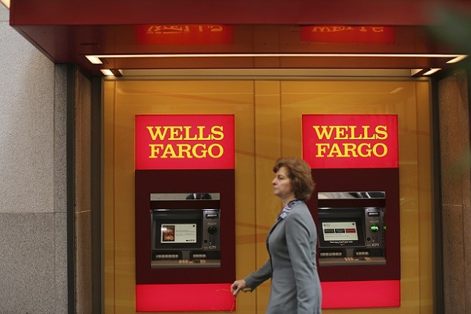 A woman walks past teller machines at a Wells Fargo bank in San Francisco, California October 10, 2013. Wells Fargo & Co reports its third-quarter results on Friday before the market's open and the options market is implying about a 2.75 percent one-day move on earnings, according to RiskReversal.com in an earnings preview on Wednesday. The shares have realized an average move of about 1.75 percent over the past four quarters and an average move of about 2.75 percent over the past eight annoucements.        REUTERS/Robert Galbraith  (UNITED STATES - Tags: BUSINESS) - RTX146JO