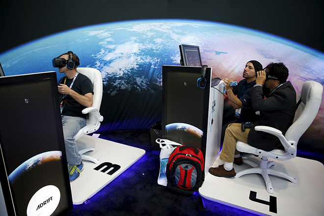 """People wear Oculus VR headsets as they play Three One Zero's """"Adrift"""" video game at the Electronic Entertainment Expo, or E3, in Los Angeles, California, United States, June 16, 2015. REUTERS/Lucy Nicholson  - RTX1GSQF"""