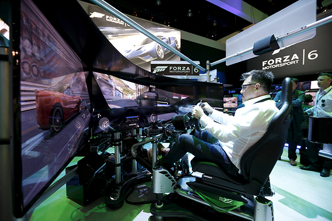 """A man plays the """"Forza Motorsport 6"""" video game simulator at the Microsoft Xbox booth at the Electronic Entertainment Expo, or E3, in Los Angeles, California, United States, June 16, 2015. REUTERS/Lucy Nicholson  - RTX1GTAT"""