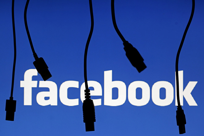 Electronic cables are silhouetted next to the logo of Facebook in this September 23, 2014 illustration photo in Sarajevo.   REUTERS/Dado Ruvic (BOSNIA AND HERZEGOVINA  - Tags: BUSINESS TELECOMS)   - RTR47HVX