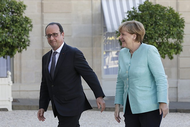 French President Francois Hollande (L) welcomes German Chancellor Angela Merkel before talks and a dinner at the Elysee Palace in Paris, France, July 6, 2015. Hollande and Merkel met in Paris on Monday evening following the Greek people's resounding 'No' to a European cash-for-reform deal in a referendum.   REUTERS/Philippe Wojazer - RTX1J9OZ