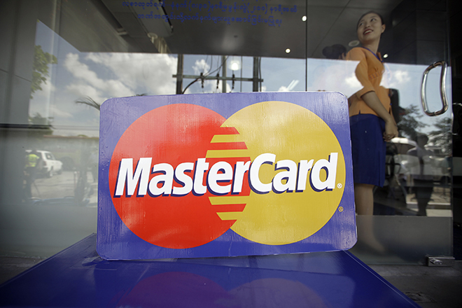 An employee stands behind a MasterCard logo during the launch of the international credit card issuer's first ATM transaction in Myanmar, in Yangon November 15, 2012.REUTERS/Soe Zeya Tun (MYANMAR - Tags: BUSINESS LOGO) - RTR3AFN3