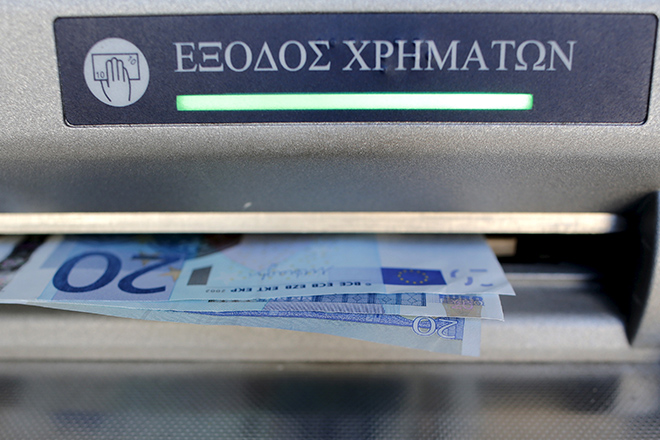 Sixty Euros, the maximum amount allowed after the imposed capital controls in Greek banks, are seen during a withdrawal operation at a bank branch ATM in central Athens, Greece, July 12, 2015. Skeptical euro zone finance ministers demanded on Saturday that Greece go beyond painful austerity measures accepted by Prime Minister Alexis Tsipras if he wants them to open negotiations on a third bailout for his bankrupt country to keep it in the euro.  REUTERS/Christian Hartmann  - RTX1K1WO
