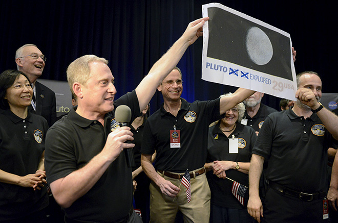 "NASA Principal Investigator for New Horizons mission Alan Stern (L) and Co-Investigator Will Grundy (R) hold up an enlarged, out-dated U.S. postage stamp with the ""NOT YET"" crossed out, during the celebration of the spacecraft New Horizons flyby of Pluto, at NASA's Johns Hopkins Applied Physics Laboratory in Laurel, Maryland, July 14, 2015. The flyby, which culminated after almost ten years of flight and over three billion miles, will allow New Horizons to photograph and collect data in the coming months.                            REUTERS/Mike Theiler      TPX IMAGES OF THE DAY      - RTX1KA2F"