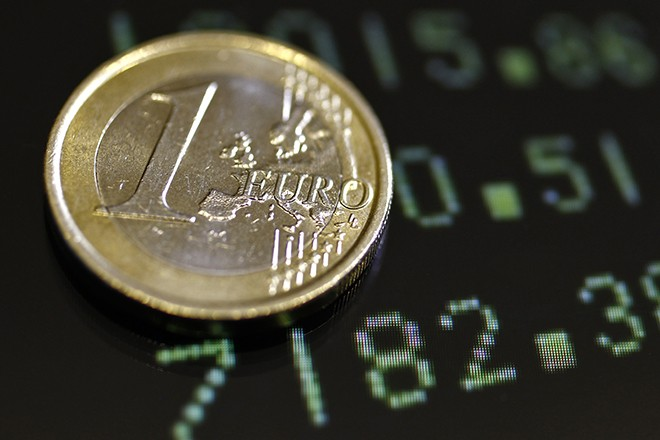 A picture illustration shows a one euro coin on a flat screen displaying exchange rates in Rome December 8, 2011. Standard & Poor's has warned it may carry out an unprecedented mass downgrade of euro zone countries, including Germany and France, if EU leaders fail to deliver a convincing agreement on how to solve the region's debt crisis in a summit on Friday. REUTERS/Stefano Rellandini (ITALY - Tags: BUSINESS) - RTR2UZUK