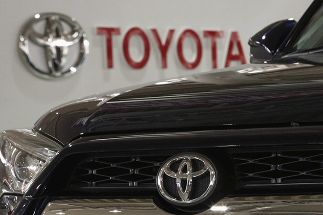 A logo of Toyota Motor Corp is pictured on a car and the background at the company's showroom in Tokyo, Japan, June 16, 2015. Toyota Motor Corp shareholders approved a controversial new class of stock on Tuesday that will bring in more long-term investors, but which faced opposition from foreign funds as they are readily available only in Japan. REUTERS/Yuya Shino - RTX1GO56