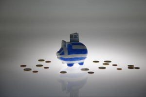 A piggybank painted in the colours of the Greek flag with a 20 euro banknote in it's slot, stands amongst various euro coins in this picture illustration taken in Berlin, Germany June 30, 2015. The head of the European Commission made a last-minute offer to try to persuade Greek Prime Minister Alexis Tsipras to accept a bailout deal he has rejected before a referendum on Sunday which EU partners say will be a choice of whether to stay in the euro. But Greek government sources said the leftist premier stood by his rejection of the creditors' conditions and Greece would default on a crucial repayment due to the International Monetary Fund on Tuesday, plunging it deeper into financial crisis. REUTERS/Pawel Kopczynski  - RTX1IDVJ