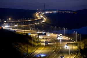 """TO GO WITH AFP STORY BY BEN PERRY Traffic passes along the M62 motorway at night near the town of Shaw in Greater Manchester, north west England on April 7, 2015. As a general election looms, the Conservative-Liberal Democrat government is holding out its """"Northern Powerhouse"""" programme as a key achievement and promising greater economic clout to boot. Manchester, which was at the forefront of Britain's industrial revolution, is again leading the way among its northern neighbours. AFP PHOTO / OLI SCARFF        (Photo credit should read OLI SCARFF/AFP/Getty Images)"""