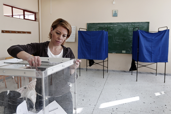 A woman prepares a ballot box at an Athens high school that will be used as a polling station January 23, 2015. An early national election will be held on January 25 after the Greek parliament failed to elect a president. REUTERS/Alkis Konstantinidis (GREECE - Tags: POLITICS ELECTIONS) - RTR4ML0J