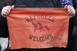 A protester holds a tissue with text 'Refugees Welcome' during an anti-Nazi demonstration in Berlin's Landsberger Allee, November 22, 2014. REUTERS/Hannibal Hanschke (GERMANY  - Tags: POLITICS CIVIL UNREST)   - RTR4F4XM