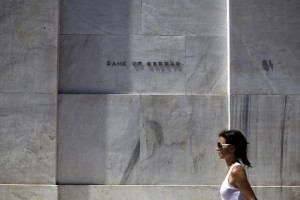 A woman walks past the headquarters of the Bank of Greece in Athens, Greece, August 19, 2015. German Finance Minister Wolfgang Schaeuble urged lawmakers to back a third bailout for Greece in a vote on Wednesday, saying while there were no guarantees of success, it would be irresponsible not to give Greeks the chance for a new start.   REUTERS/Stoyan Nenov  - RTX1OR1R