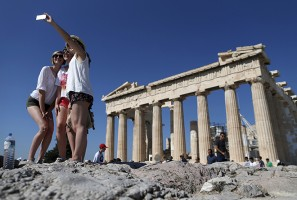 A group of tourists take a selfie in front of the temple of the Parthenon atop the Acropolis in Athens, Greece July 9, 2015. A race to save Greece from bankruptcy and keep it in the euro gathered pace on Wednesday when Athens formally applied for a three-year loan and European authorities launched an accelerated review of the request. REUTERS/Christian Hartmann  - RTX1JO1X