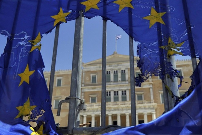 A burned EU flag hangs on  the barriers protecting the Greek  parliament in Athens  on May 1, 2013. Greece's two main unions called a general strike against prolonged austerity on May 1,  with protests by unions, students and workers.  AFP PHOTO/ LOUISA GOULIAMAKI        (Photo credit should read LOUISA GOULIAMAKI/AFP/Getty Images)