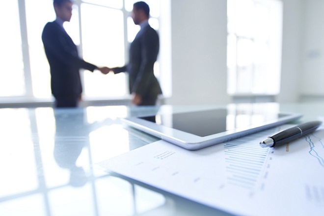 Financial report, digital tablet and pen on office table; two business people shaking hands in the background