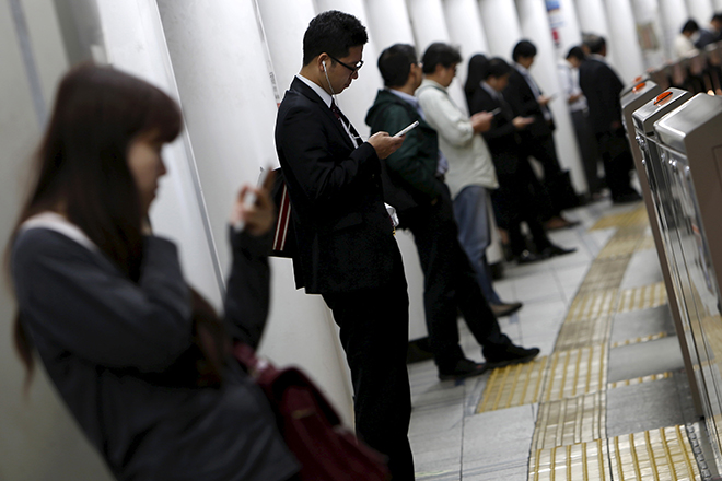 People look at their mobile phones while waiting for a train at a subway station in Tokyo, Japan, October 14, 2015.  Japanese manufacturers' confidence worsened for the second straight month and is expected to fade going forward, a Reuters poll showed, adding to lingering fears of a recession and keeping policymakers under pressure to deploy fresh stimulus. Picture taken October 14, 2015. REUTERS/Yuya Shino - RTS4I8I