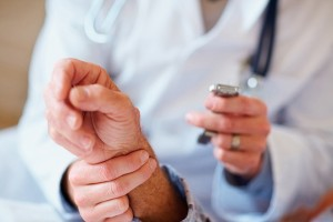Closeup of a doctor checking an old man's pulse , focus on hands