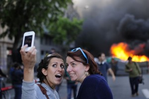 Tourists take a 'selfie' picture as demonstrators burn a trash container during a May Day rally in Barcelona, Spain, Thursday, May 1, 2014. Tens of thousands of workers marked May Day in European cities with a mix of anger and gloom over austerity measures imposed by leaders trying to contain the eurozone's intractable debt crisis. (AP Photo/Manu Fernandez)