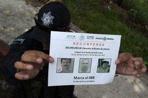 "epa04849752 A police officer shows a reward notice as investigators and members of Federal Police continue investigations into the escape of drug trafficker Joaquin ""El Chapo"" Guzman, in Amolaya, Mexico, 16 July 2015. Joaquin 'Chapo' Guzman, considered one of Mexico's most powerful drug lords, made his second escape on 11 July from a high-security prison using a series of tunnels, Mexican authorities confirmed 12 July. Guzman left his cell through a tunnel that started in his shower in the central Mexican Altiplano prison in the town of Almoloya de Juarez on 11 July. The tunnel, which had lighting, ventilation systems and rails that Guzman's men purportedly used to remove the rubble as they worked, led to an empty building about 1.5 kilometres away, officials said.  EPA/Alex Cruz"