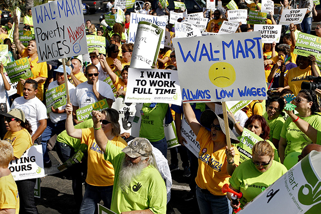 Striking Walmart workers gather during a rally to protest unsafe working conditions and poor wages outside a Walmart store in Pico Rivera, California, October 4, 2012. About 50 workers from nine stores in Los Angeles County walked off the job Thursday morning to protest what they say are unfair labor practices by Wal-Mart Stores Inc, sponsors of the action said. REUTERS/Jonathan Alcorn (UNITED STATES - Tags: POLITICS CIVIL UNREST BUSINESS EMPLOYMENT) - RTR38T40