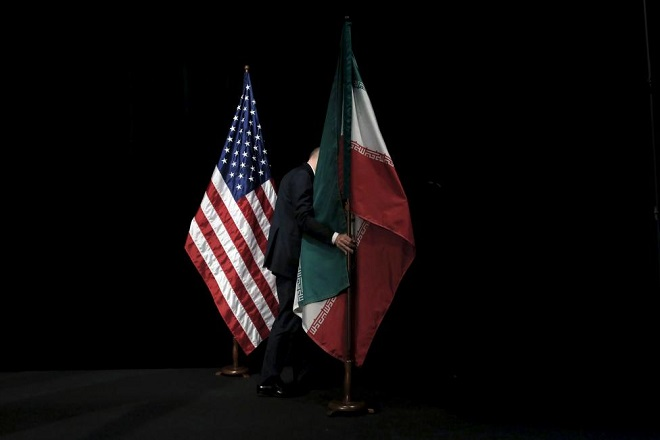 "A staff member removes the Iranian flag from the stage after a group picture with foreign ministers and representatives of Unites States, Iran, China, Russia, Britain, Germany, France and the European Union during the Iran nuclear talks at the Vienna International Center in Vienna, Austria July 14, 2015. Iran and six major world powers reached a nuclear deal, capping more than a decade of on-off negotiations with an agreement that could potentially transform the Middle East, and which Israel called an ""historic surrender"". REUTERS/Carlos Barria"