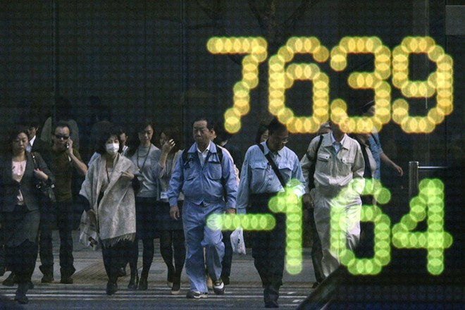 epaselect epa05027675 Pedestrians are reflected in a stock market indicator board in Tokyo, Japan, 16 November 2015. Stocks across Asia were down in the first day of trading after the Paris terrorist attacks which left about 130 people dead. Japan's benchmark Nikkei 225 Stock Average closed down by 1.04 percent. Earlier in the day, the government announced that Japan sunk back into recession for the second time since Shinzo Abe became prime minister three years ago. Gross domestic product fell at an annualized rate of 0.8 percent in the third quarter from July to September.  EPA/FRANCK ROBICHON