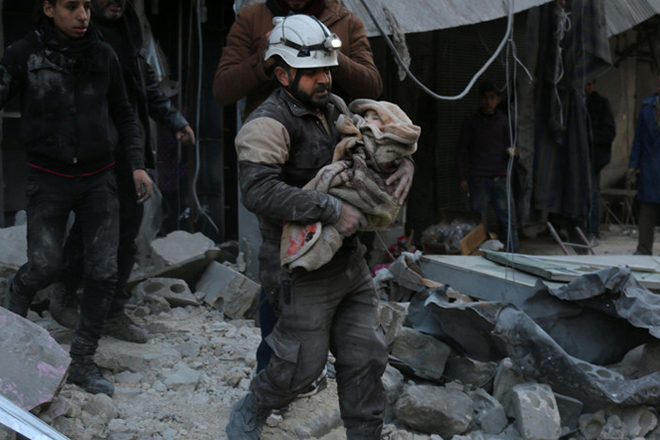A Syrian Civil Defence worker carries a child wrapped in a blanket over the rubble following a reported air strike by Syrian government forces on the Sukkari neighborhood of Syria's northern city of Aleppo, on January 16, 2016.  At least 35 Syrian soldiers and pro-regime militiamen were killed in a multi-front attack by the Islamic State group on the eastern city of Deir Ezzor, a monitor said. The fighting came as regime forces battled Islamic State (IS) jihadists in the northern province of Aleppo, repelling a jihadist assault and killing at least 16 fighters from the group.   / AFP / Karam Al-Masri