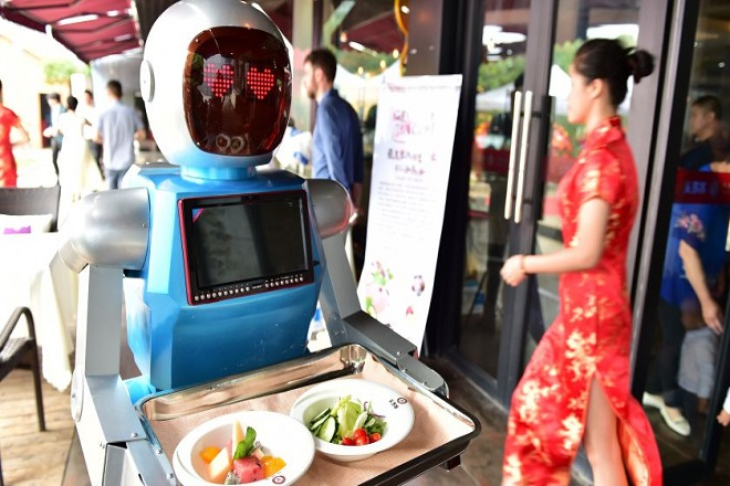 """YIWU, CHINA - MAY 18: (CHINA OUT) A """"male"""" robot waiter delivers meals for customers at robot-themed restaurant on May 18, 2015 in Yiwu, Zhejiang province of China. Sophomore Xu Jinjin in 22 years old from Hospitality Management of Yiwu Industrial and Commercial College managed a restaurant where a pair of robot acted as waiters. The """"male"""" one was named """"Little Blue"""" (for in blue color) and the """"female"""" one was """"Little Peach"""" (for in pink) and they could help order meals and then delivered them to customers along the magnetic track and said: """"Here're your meals, please enjoy"""". According to Xu Jinjin, They had contacted with the designer to present more robot waiters to make the restaurant a real one that depends completely on robots. (Photo by ChinaFotoPress/ChinaFotoPress via Getty Images)"""