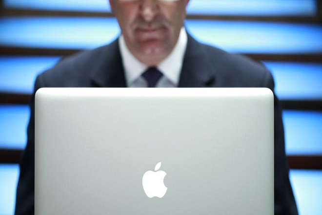 A businessman uses an Apple Macbook Pro laptop computer, made by Apple Inc., to surf the web in this arranged photograph in London, U.K., on Thursday, Aug.19, 2010. Research In Motion Ltd. is turning to technology used in BMW  audio systems and the Army?s Crusher tank as it tries to distinguish its new tablet computer from Apple Inc.?s iPad, said three people familiar with the plans. Photographer: Jason Alden/Bloomberg via Getty Images