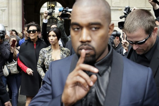 Kim Kardashian (C) pushes a stroller next to her partner Kanye West (front) and her mother Kris Jenner (2L) as they leave their hotel on May 23, 2014 in Paris. Hip hop star Kanye West and reality TV celebrity Kim Kardashian are expected to tie the knot this weekend, fuelling speculation about the wedding's location. AFP PHOTO/KENZO TRIBOUILLARD        (Photo credit should read KENZO TRIBOUILLARD/AFP/Getty Images)