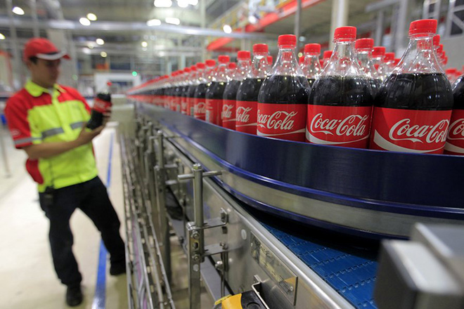 epa05151455 (FILE) A file photo dated 31 March 2015 showing an Indonesian worker standing next to Coca-Cola products in the Coca Cola Amatil Indonesia (CCAI) Cikekodan Plant in Bekasi, West Java, Indonesia. The Coca-Cola Company, the world's largest beverage company, released their fourth quarter 2015 financial results on 09 February 2016 saying their 2015 financial performance was 'slightly ahead of expectations'. The profits stood at 1,2 billion USD, compared with the previous year result of 770 million USD. Sales in the same period fell to 10 billion USD, a drop of 8 per cent.  EPA/BAGUS INDAHONO