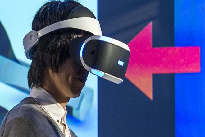 An exhibitor shows off the new Sony Corp. Project Morpheus virtual-reality headset at an event during the 2015 Game Developers Conference (GDC) in San Francisco, California, U.S., on Tuesday, March 3, 2015. Sony will begin selling its virtual-reality headset in the first half of 2016, according to Shuhei Yoshida, president of Worldwide Studios at Sony Computer Entertainment. The device will have a 5.7-inch screen, he said. Photographer: David Paul Morris/Bloomberg via Getty Images